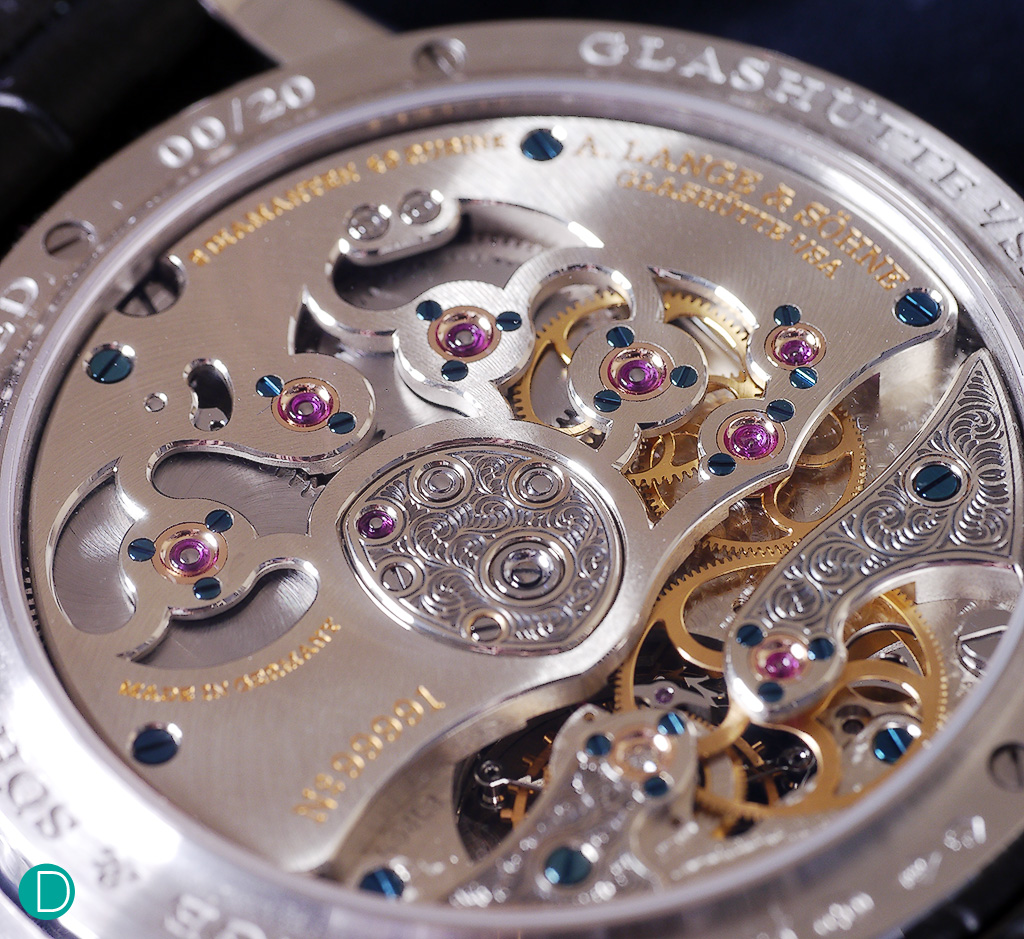The Lange caliber L961.3. With hand engraving on the two cocks and the central medallion. Note also the many inwrd and outward angles on the openings on the 3.4 plate to show the double barrels and part of the movement wheels.  These are particularly difficult to execute perfectly, and the way it is delivered here shows Lange's mastery.