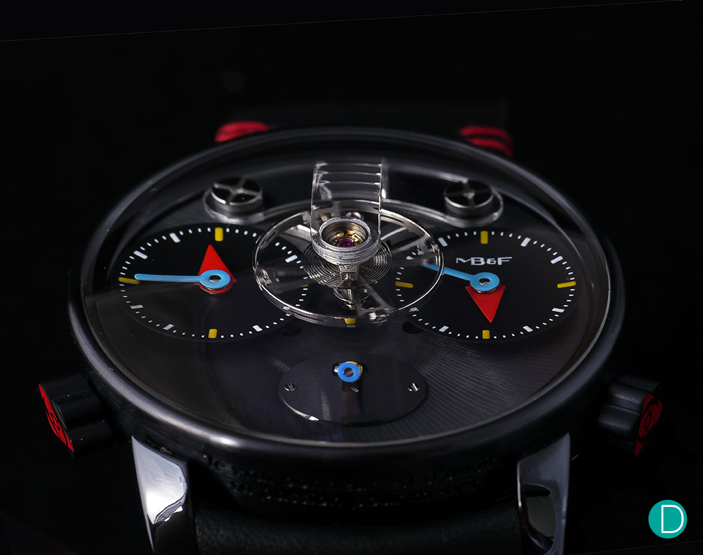 In black PVD treated titanium, watch takes on a different persona. Even with the use of bright colors, the overhanging feel is of a deep dark soul within. The beating balance which seems to float over the dial helps with this illusion.